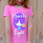 Girl looking down at her Hearts In My Eyes Lolligag shirt