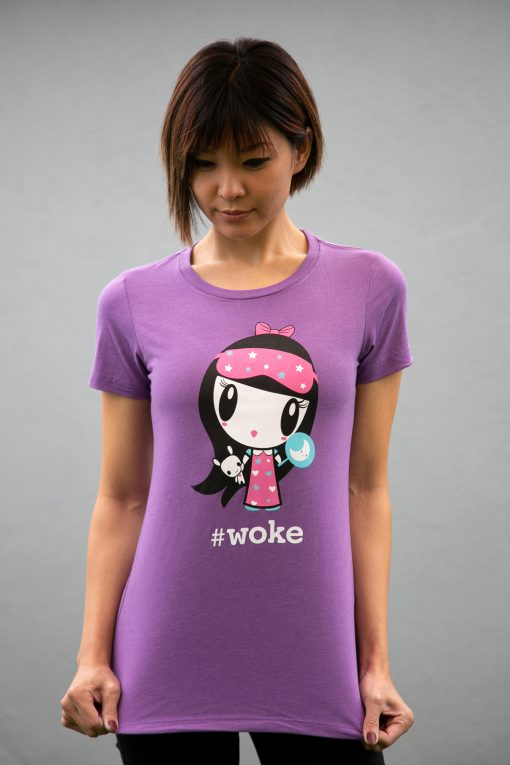 A woman wearing a tee shirt featuring Lolligag in a nightgown holding a plush Moot with the word woke