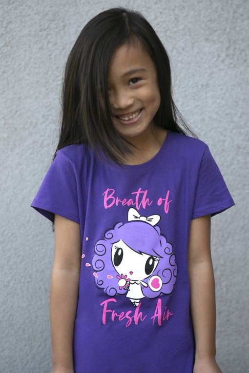 Girl wearing a shirt featuring Lolligag holding a flower with petals blowing in the wind