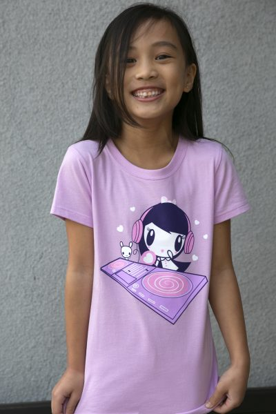 Girl wearing a shirt that features Lolligag and Moot behind a turntable spinning records