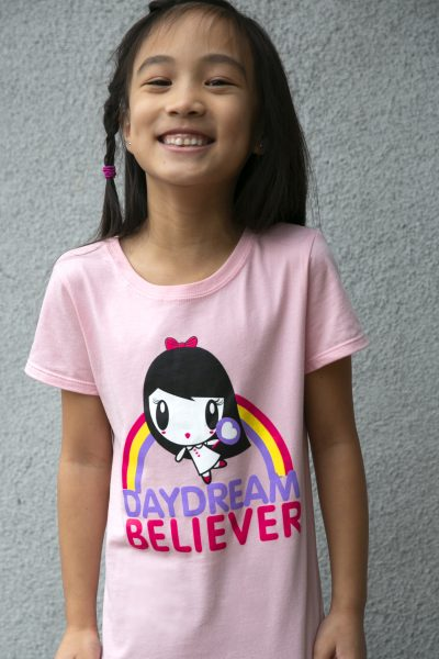 A girl wearing a shirt featuring Lolligag dancing in front of a rainbow