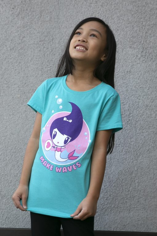 Girl wearing a shirt featuring Lolligag as a mermaid and the words make waves