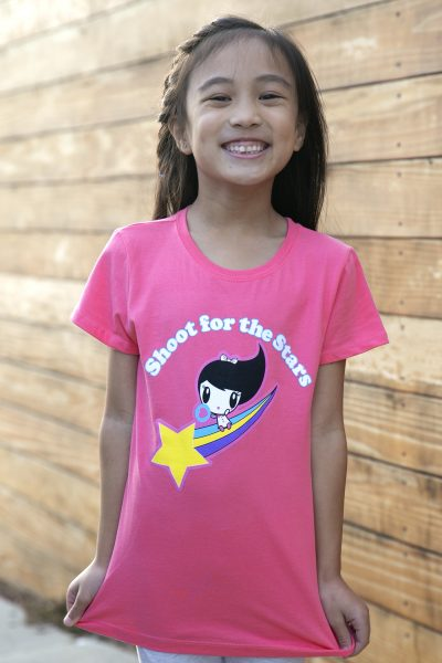 Girl wearing a shirt with Lolligag riding a rainbow tail behind a shooting star