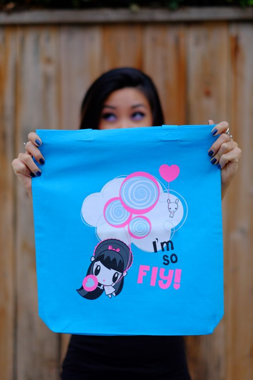 Women holding Lolligag tote with picture of Lolligag and Moot floating up holding balloons